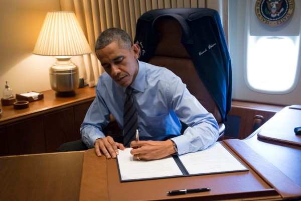 U.S. President Barack Obama signs two Presidential Memoranda associated with his Executive Actions on immigration From his office on Air Force One upon his arrival in Las Vegas Nevada November 21, 2014.