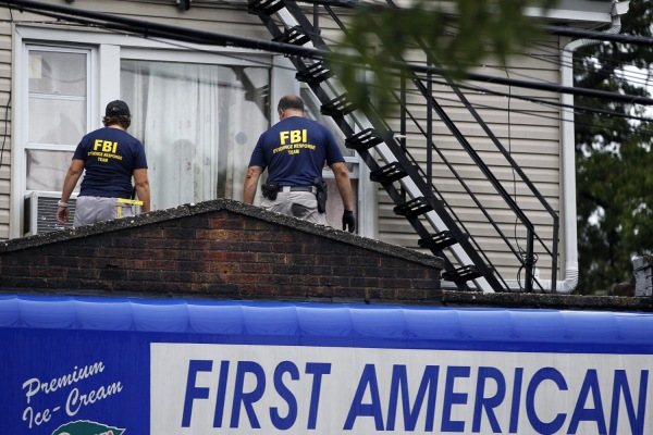 FBI agents walk around the roof outside an apartment during an investigation at a building Monday, Sept. 19, 2016, in Elizabeth, N.J. FBI agents are searching the apartment in New Jersey that is tied to Ahmad Khan Rahami wanted for questioning in the New York City bombing. (AP Photo/Mel Evans)